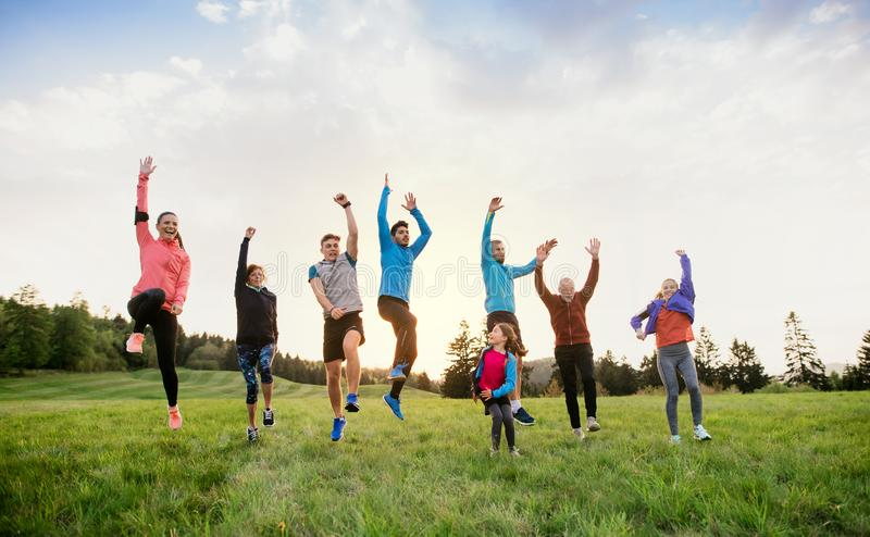 A large group of multi generation sport people standing in nature, jumping. A large group of active multi generation people running a race competition in nature stock images