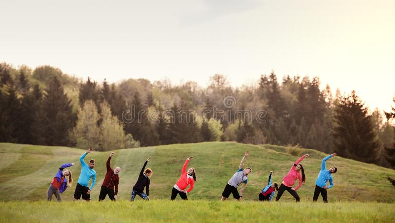 A large group of multi generation sport people standing in nature, stretching. A large group of active multi generation people running a race competition in stock photos