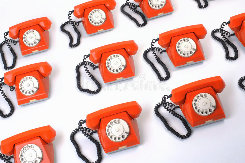 Large group of orange telephones stock image