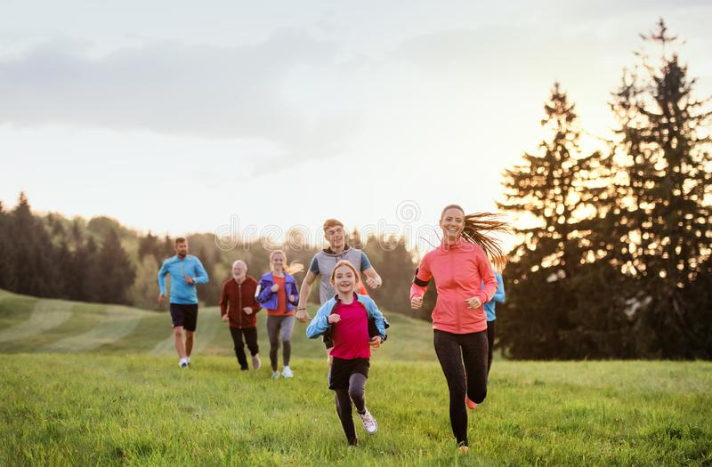 A large group of people cross country running in nature. A large group of people cross country running in nature at sunset royalty free stock photo