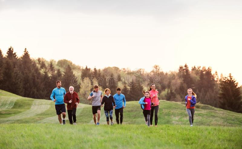 A large group of people cross country running in nature. stock photos