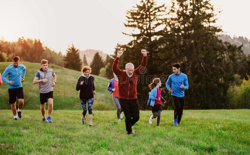 Large group of people cross country running in nature. A large group of people cross country running in nature at sunset stock photo