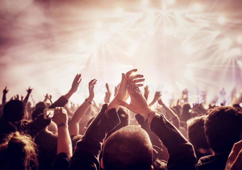 Large group of people enjoying concert. Vintage style photo of a crowd, happy people enjoying rock concert, raised up hands and clapping of pleasure, active stock image