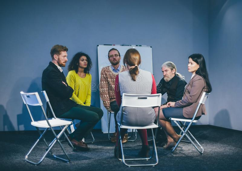 Large group of people having a counseling session. Different people in depression sitting at counseling session with therapist. Toned concept royalty free stock photo