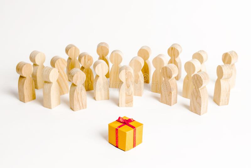 A large group of people looking at a gift. The concept of choosing a good gift, a limited number, all sold out. A gift for the. Community. Birthday party, New stock photo