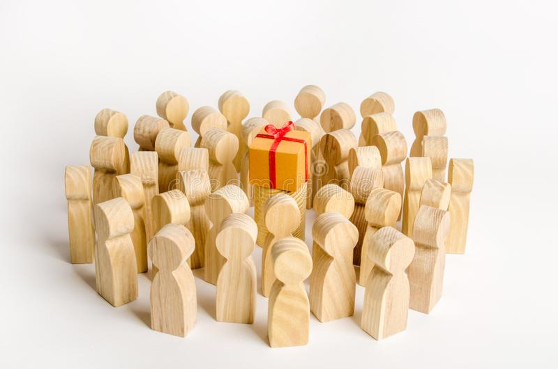 A large group of people surrounds a box with a present. The concept of choosing a good gift, limited number, all sold out. A gift. For the community. Birthday stock photo
