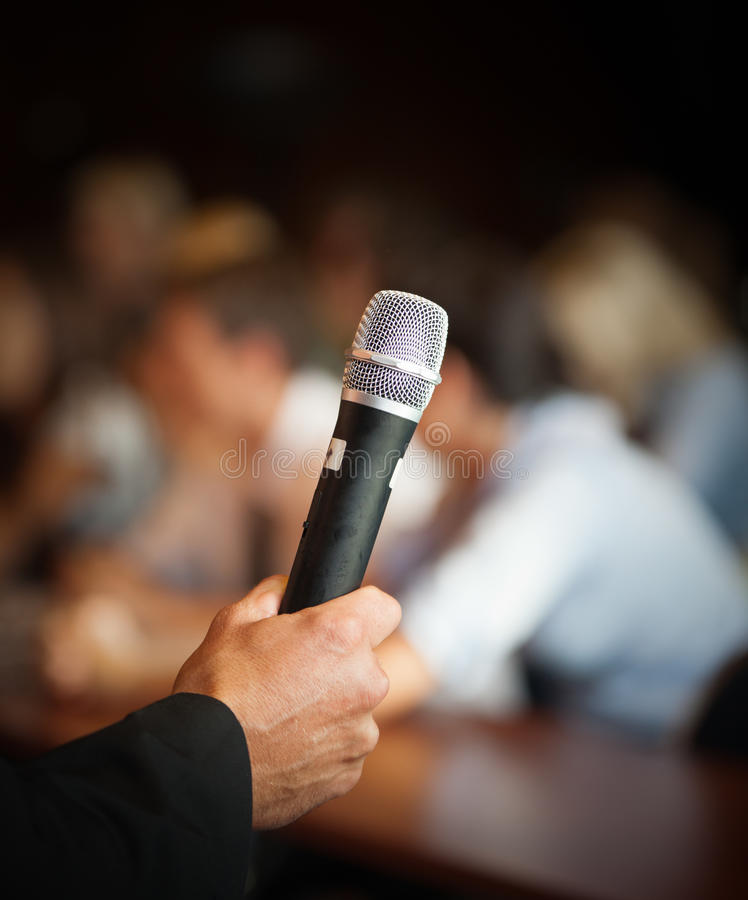 Large group of seminar audience in class room. Hand holding microphone in front of large group of people in class room, audience in professional education royalty free stock photography