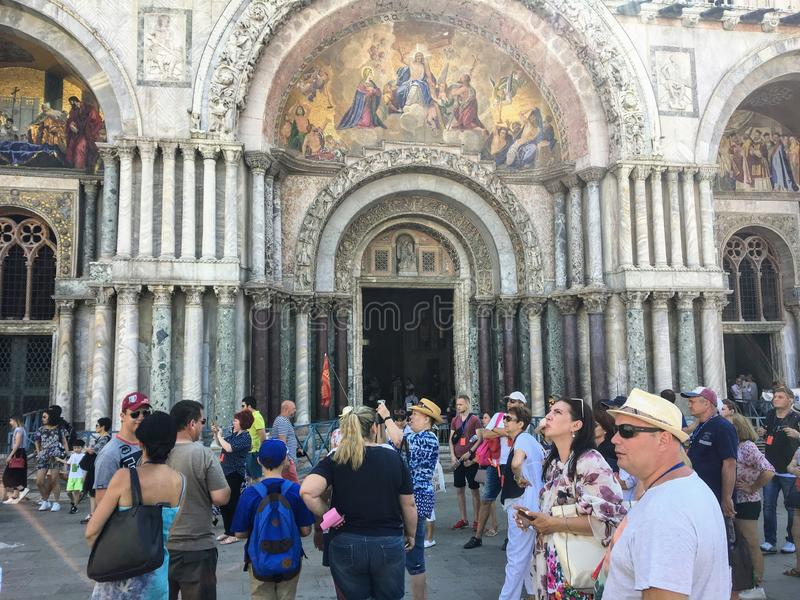 A large group of tourists outside St. Marks Basilica in St. Marks square taking photos and enjoying the sights on a hot summer day stock photography