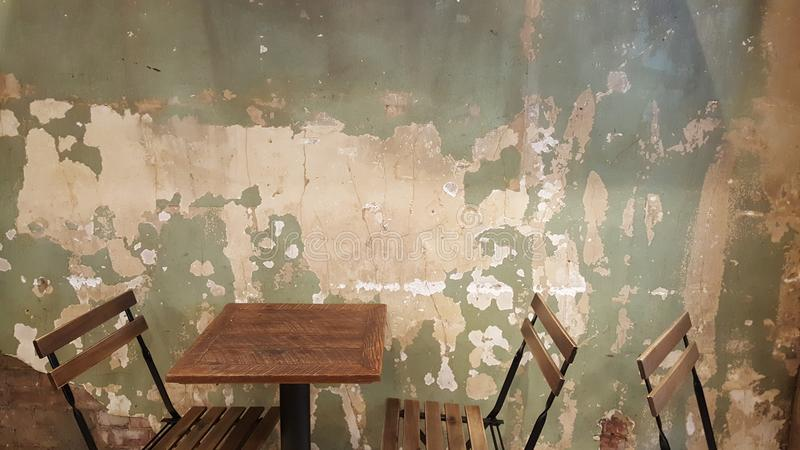 restaurant folding chairs and tables with distressed and chipping white green wall stock image
