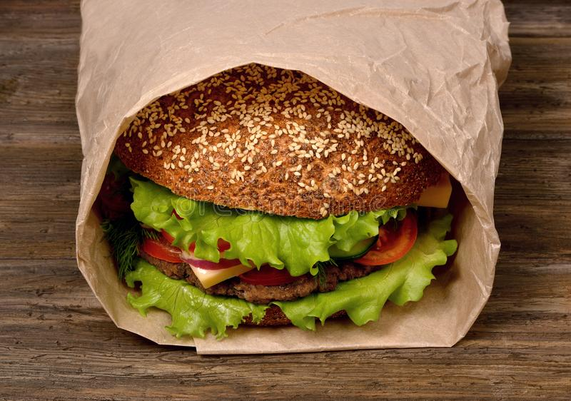 Large hamburger on a wooden table is packed in a paper bag royalty free stock photos