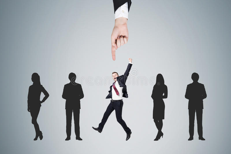 Large hand picking up people near a gray wall. Large hand is picking up a men in suit from a row of candidates. Concept of recruiting and finding the right stock image