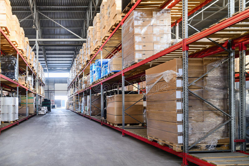 Large hangar warehouse industrial and logistics companies. Boxes and containers with goods placed on high shelves stock photo