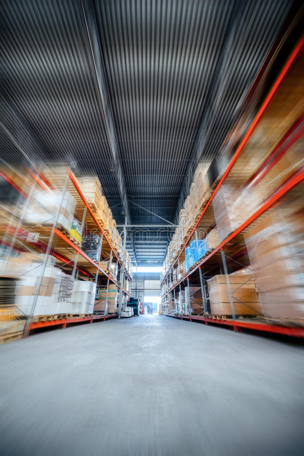 Large hangar warehouse industrial and logistics companies. Warehousing on the floor and called the high shelves. Toning the image. Motion blur effect stock photography