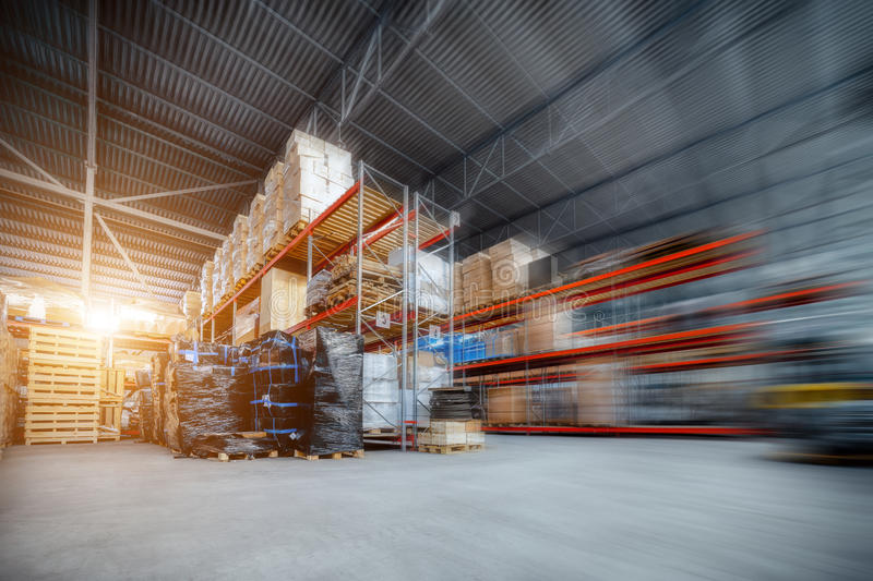 Large hangar warehouse industrial and logistics companies. Warehousing on the floor and called the high shelves. Toning the image. Motion blur effect. Bright royalty free stock image
