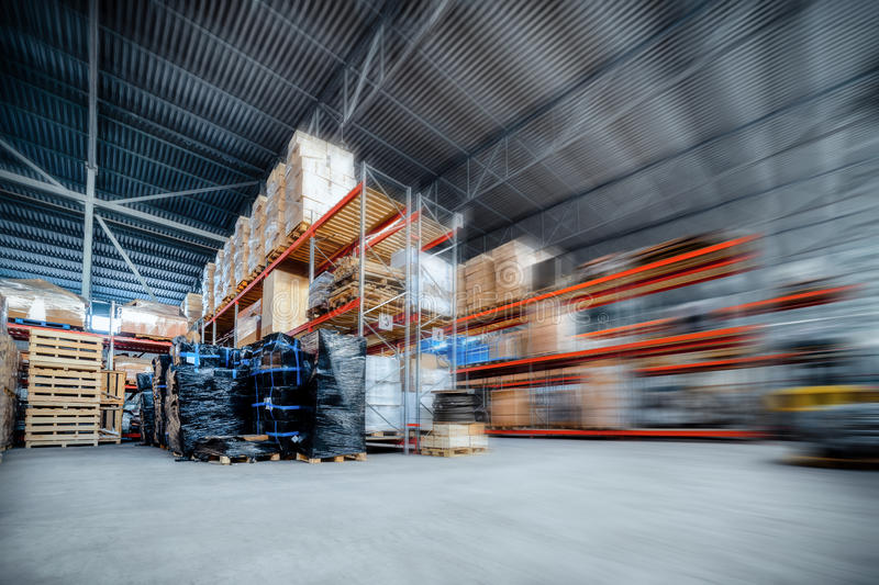 Large hangar warehouse industrial and logistics companies. Warehousing on the floor and called the high shelves. Toning the image. Motion blur effect stock images