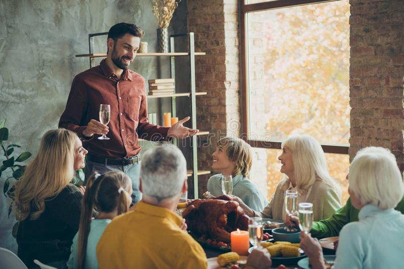 Large happy familly gathering on october event party thanksgiving day sit table enjoy meal roast meat corn man stand royalty free stock photo
