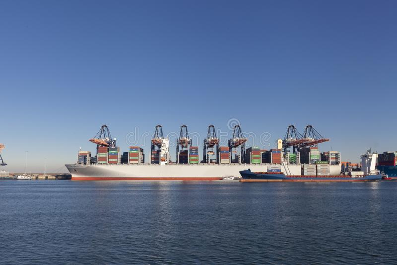 Large harbor cranes loading container ships in the port of Rotterdam stock photography
