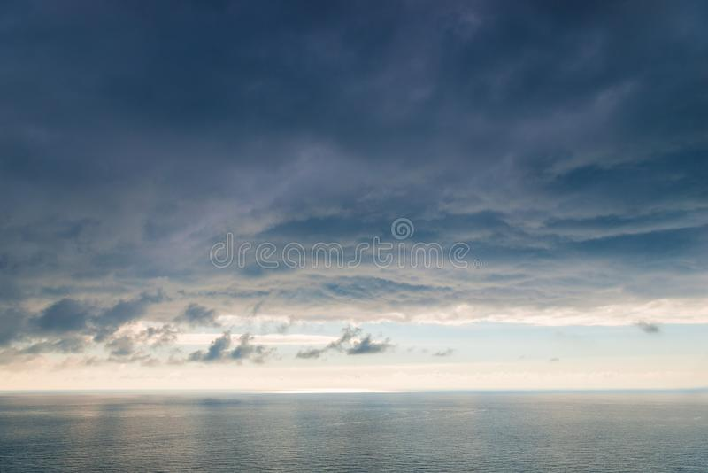 Large heavy black cloud dramatic sky above the sea surface stock photo
