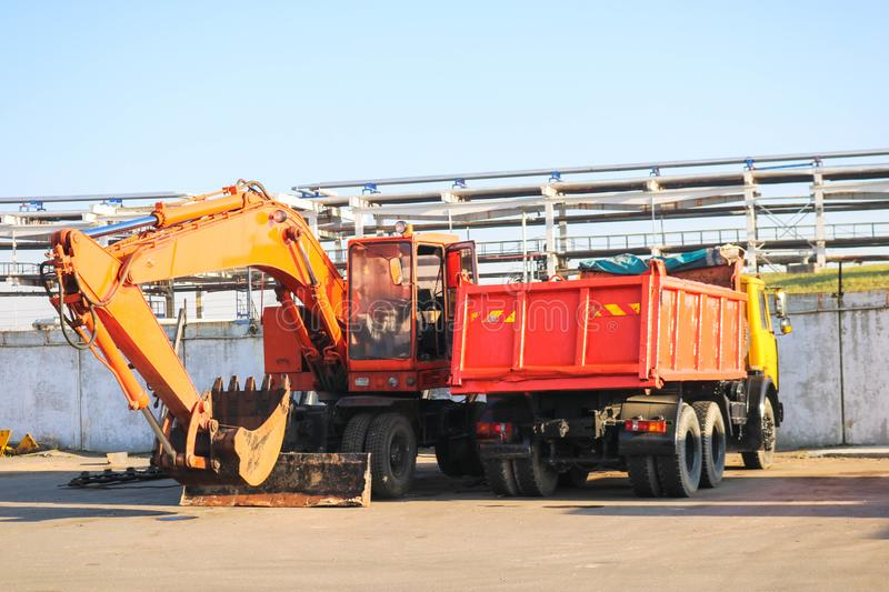A large heavy yellow orange truck with a trailer, a dump truck and an excavator with a ladle are parked in a row at a construction stock images