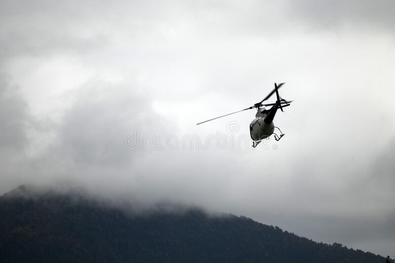 Helicopter heading off to the hills stock photo