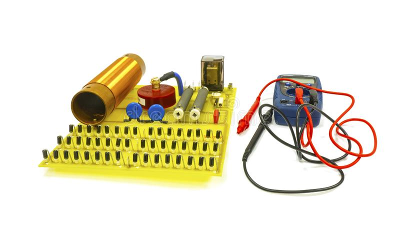 Large high-voltage electrical circuit board with radio elements. Nearby is a tester. Isolate stock photography