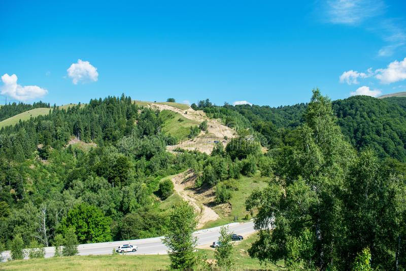 A large hill covered by pine forests near the mountains. A beautiful blue sky. Tourists stopped on the road to admire the scenery. The road crosses the hill stock photo