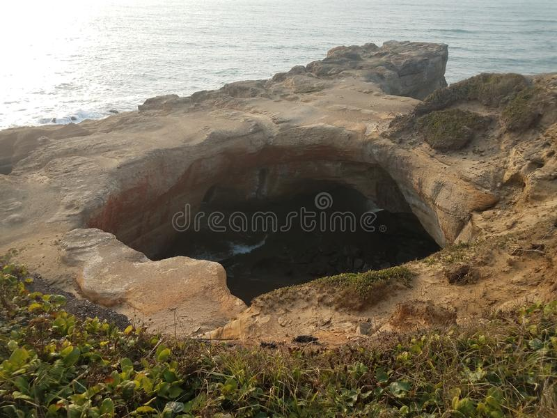 Large hole in cliff at Oregon coast with ocean and waves stock photos