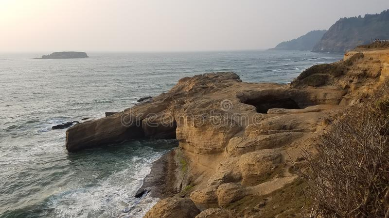 Large hole in cliff at Oregon coast with ocean and waves royalty free stock photos