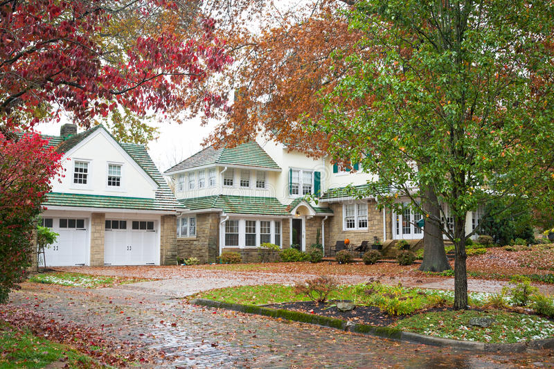 Large Home and Garage. Large American mansion made of river stone and siding, a green roof and a large two-car garage. Fall colors surround the house, the trees royalty free stock photography