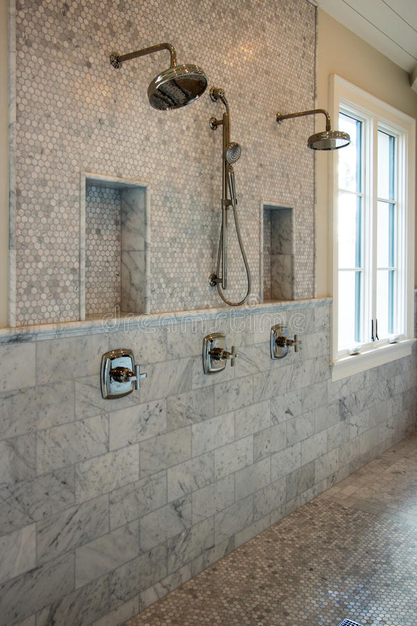 Large home interior bathroom showers. New home huge open bathroom with showers, tile walls and tile floor stock images