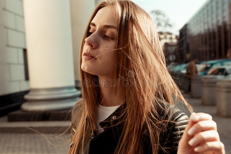 A large horizontal portrait of a young girl with blond hair against a city street stock image