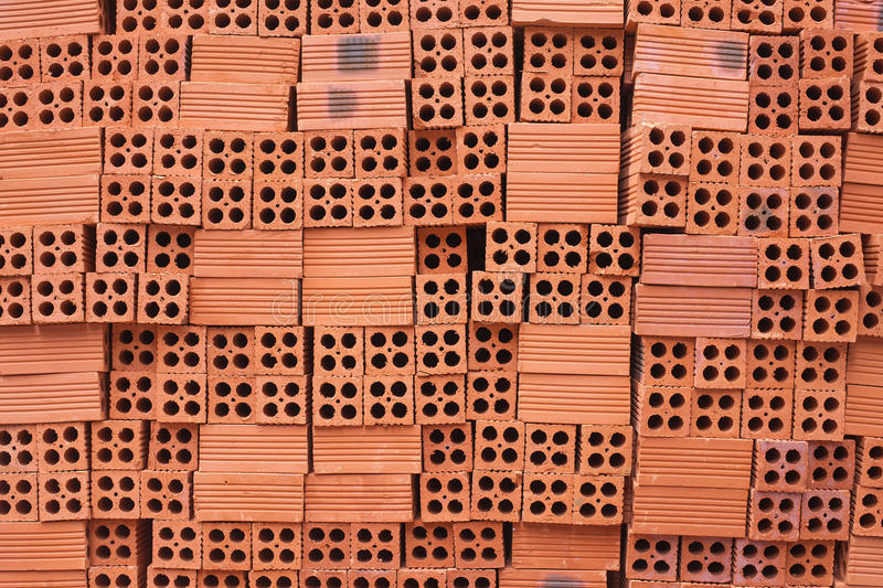 Large horizontal uneven flow of red bricks. For construction. Textural background stock photography