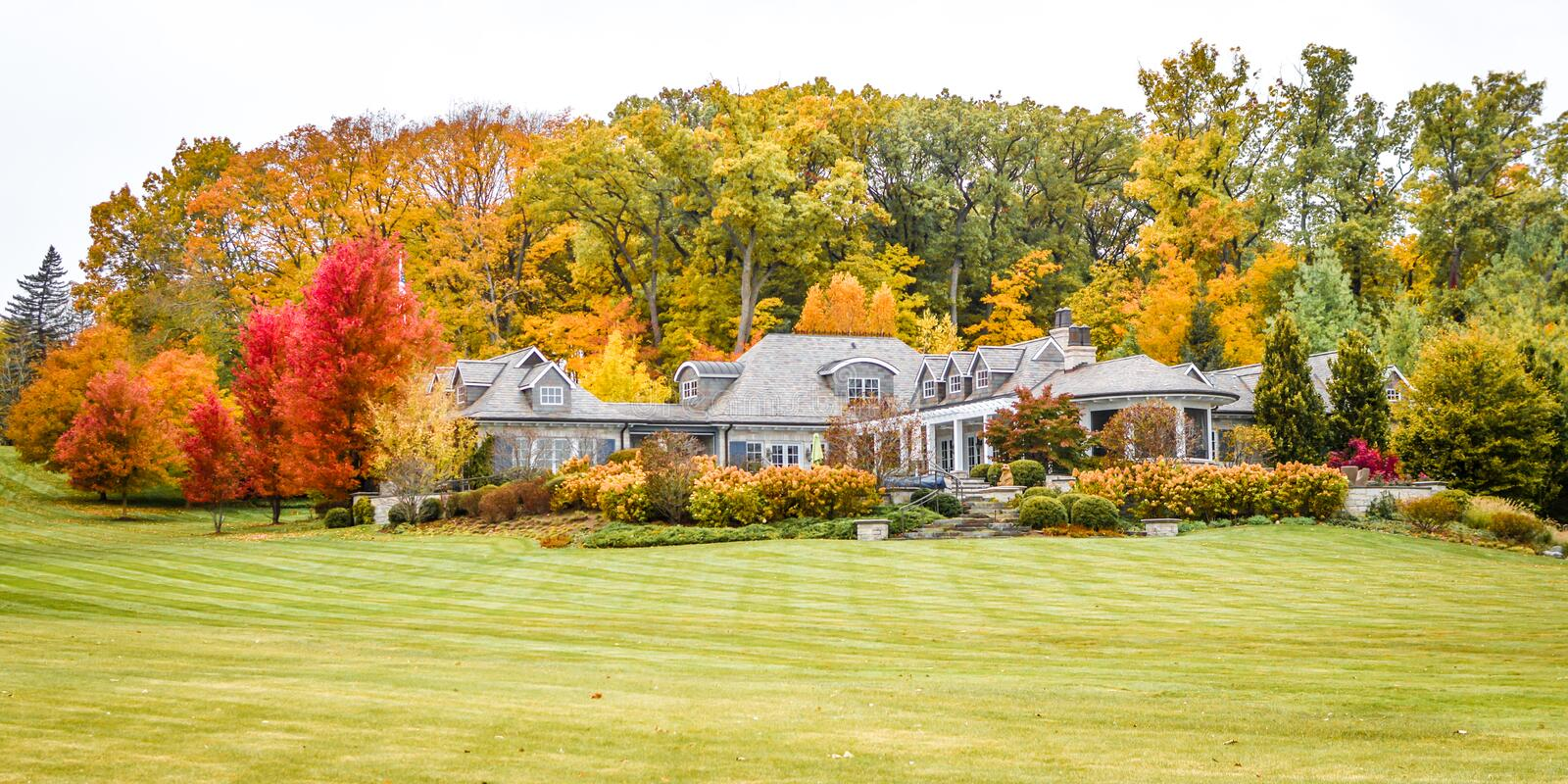 Large House in Fall, Lake Geneva, WI. A beautiful large, ranch style home in the autumn with colored trees located along the shoreline of Lake Geneva, Wisconsin royalty free stock photography