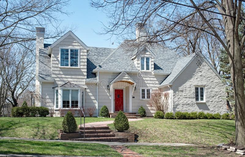Large House with White Shake Siding and Bay Window. Large, two story house with white shake siding, white painted brick garage, bay window & red front door, set stock photography