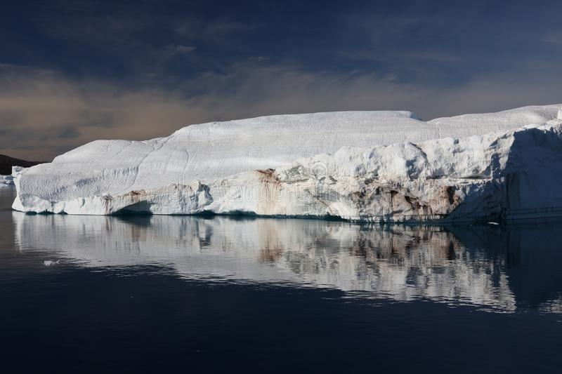 A large iceberg and its reflection in calm fjord waters in northwest Greenland stock photo