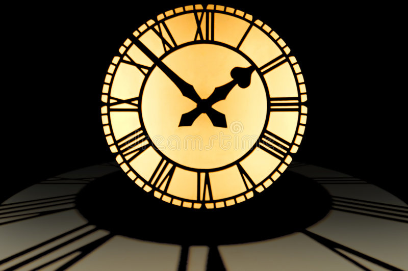 Large illuminated clock dial at ten to two on top of a circle of royalty free stock image