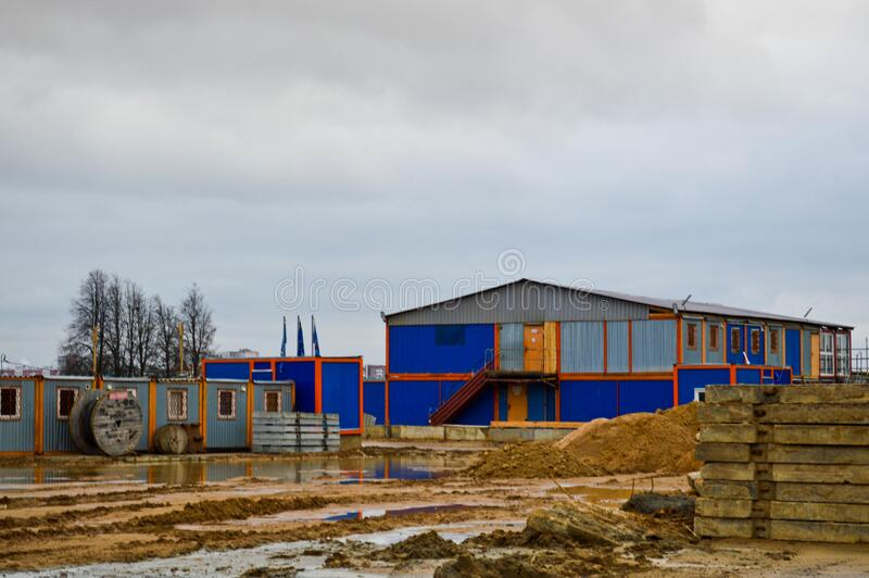 A large industrial barn warehouse and modular buildings for workers at the open-air construction site warehouse.  royalty free stock image