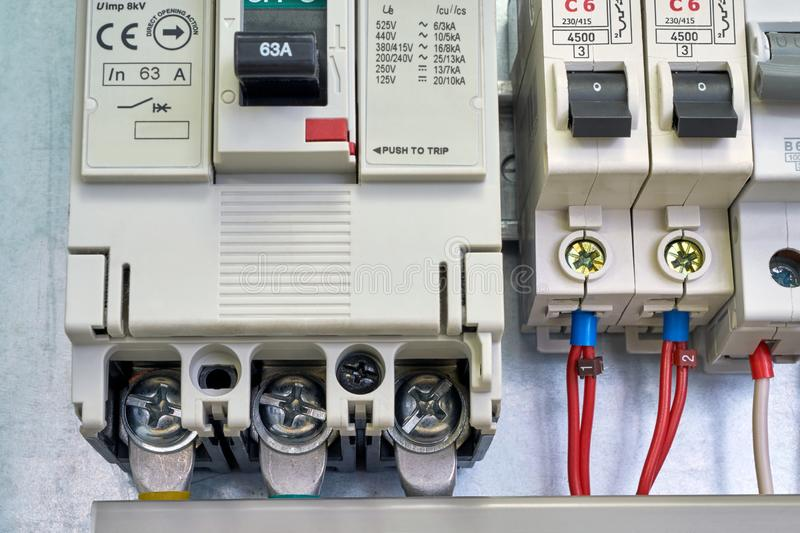 Large industrial circuit breaker and modular electrical circuit breakers. Electrical wires or cables are connected to the switches. A number of electrical stock photos