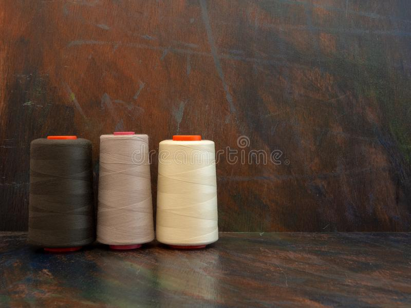 Large industrial cones of white and brown sewing threads laying and standing on a dark background. Front view studio shot. royalty free stock photo