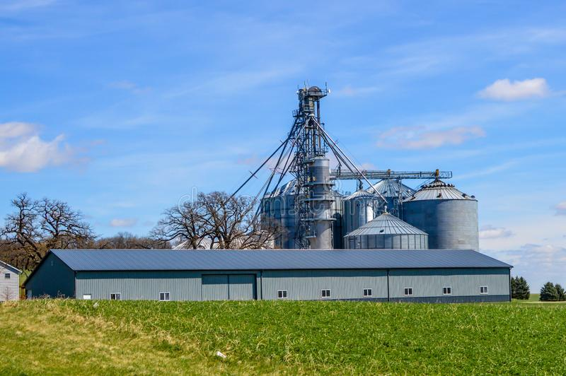 Large Industrial Farm in Lake Geneva, WI with Brock Silos. A large blue industrial barn on a farm in Lake Geneva, Wisconsin with Large Brock Grain Silos royalty free stock photos