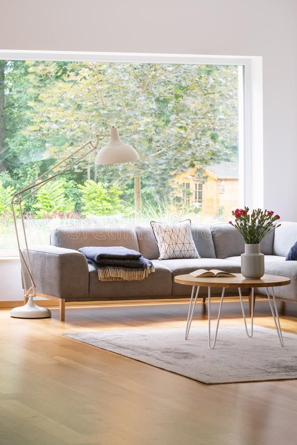 Large, industrial style floor lamp above an elegant sofa in a white and natural, scandinavian living room interior with an outside. View concept stock photos