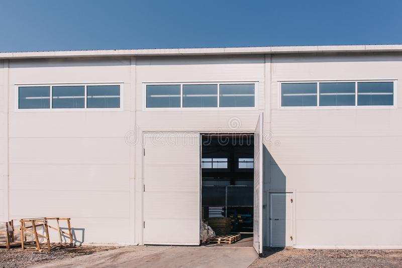 Large industrial warehouse or storehouse exterior with open gates royalty free stock photo