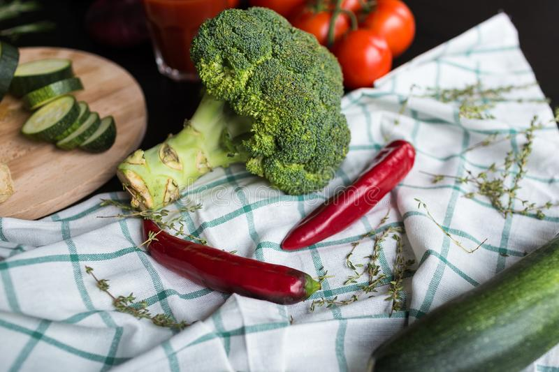 A large inflorescence of broccoli, a green squash and two red chili peppers are lying on the plaid tissue. in the stock photos