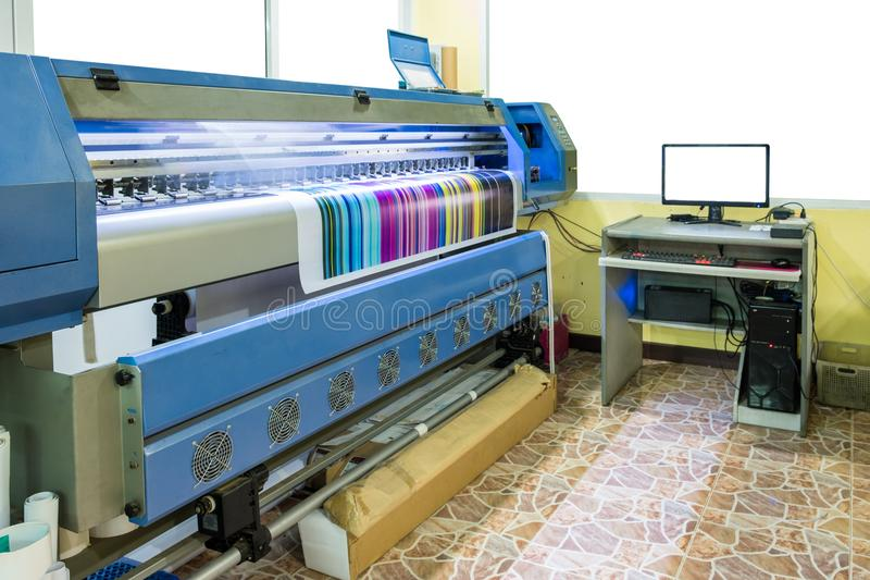 Large inkjet printer working multicolor cmyk on vinyl banner wit. H computer control in printing plant stock photo