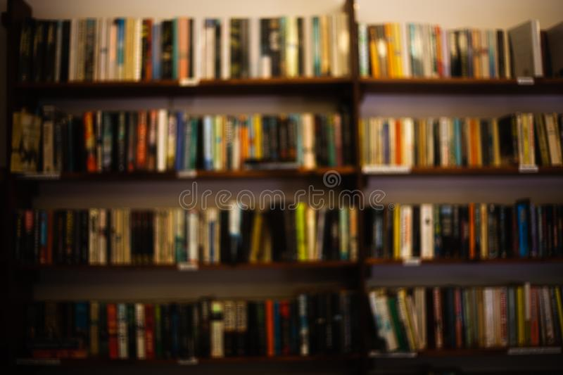 A large interior room home library with many diffirent books. Front view to wooden shelf filled with large number of books bookshe royalty free stock image