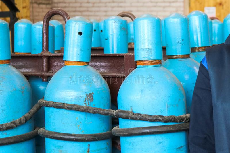 Large iron metal blue gas cylinders with oxygen, air, helium under excessive internal pressure to store compressed, liquefied and. Dissolved under pressure stock images