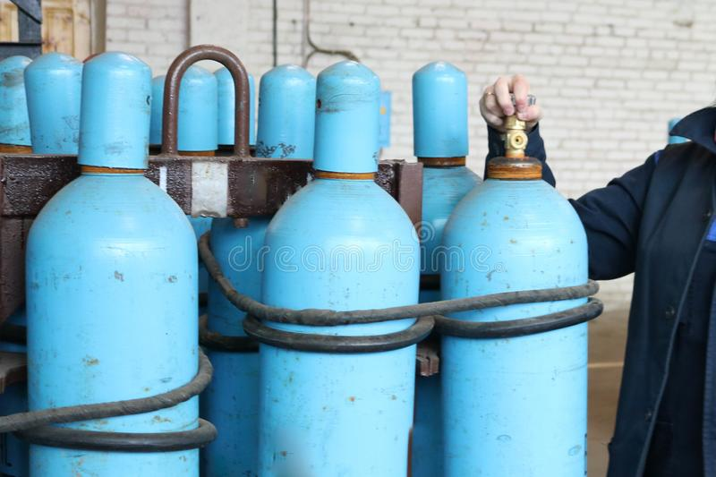 Large iron metal blue gas cylinders with oxygen, air, helium under excessive internal pressure to store compressed, liquefied and. Dissolved under pressure royalty free stock photography