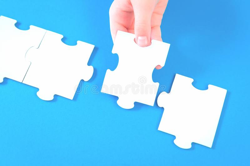 Large jigsaw puzzle pieces on blue desk stock image