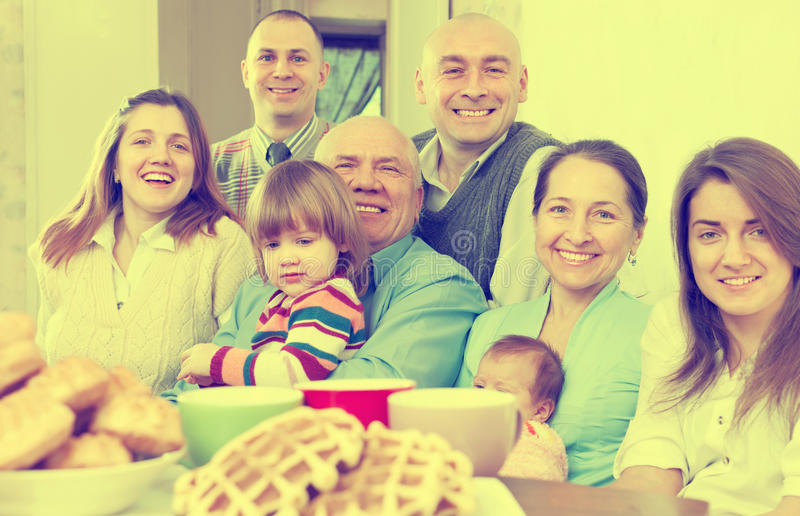 Large joyful three generations family. Sits in home stock photo