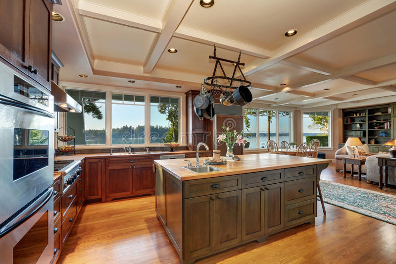 Large kitchen island with hanging pot rack above stock photography